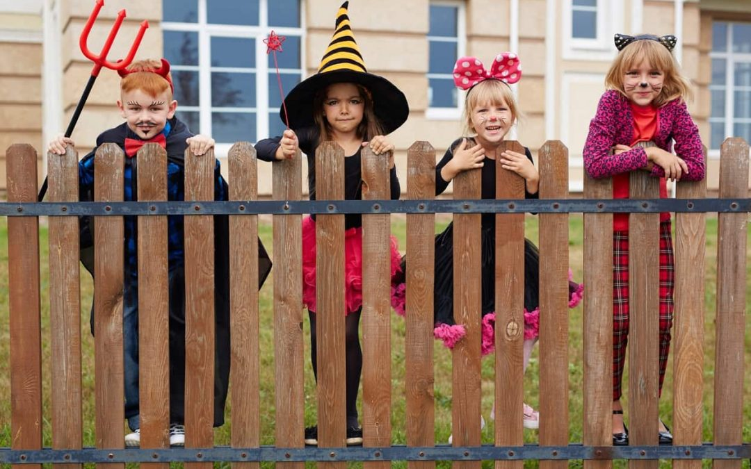 Children with nice teeth standing along a fence while dressed for Halloween.