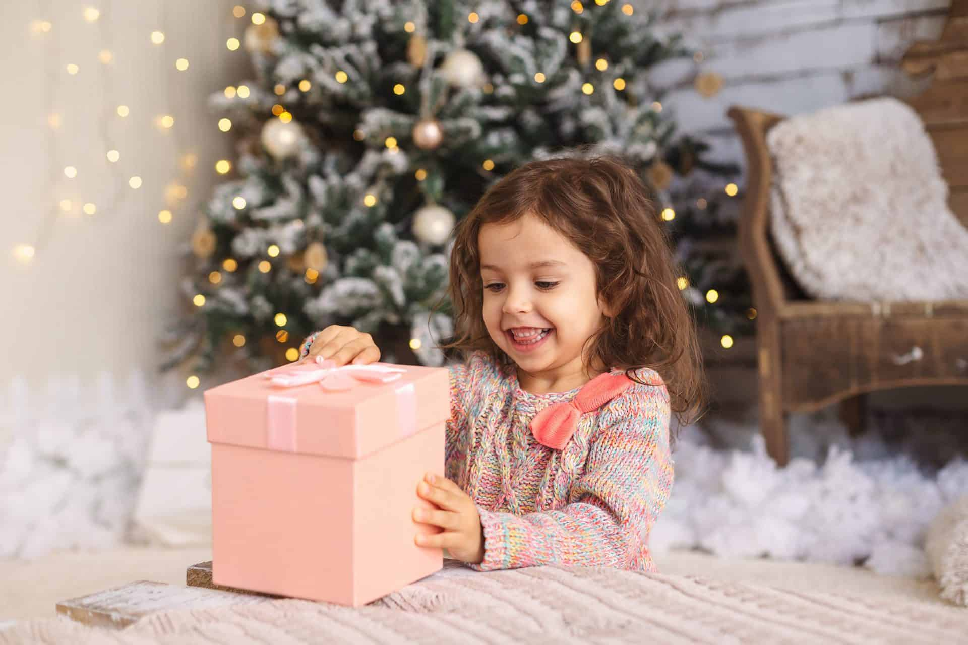 little girl smiling, opening gifts