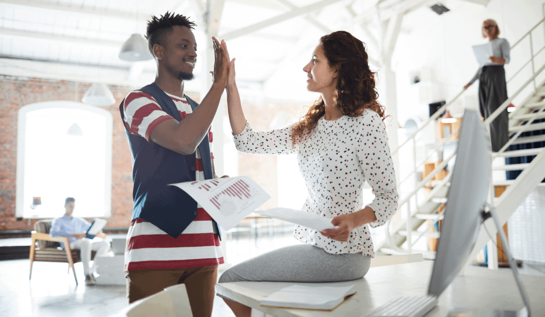 man and woman high fiving in an open-plan office
