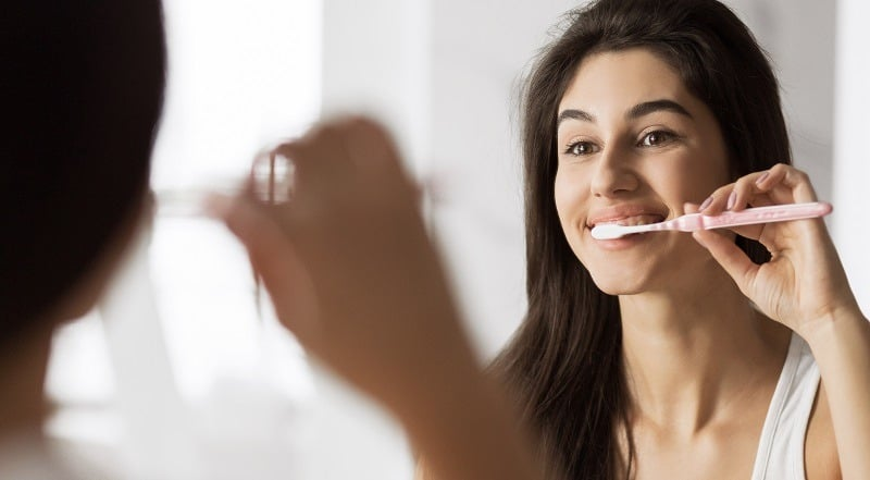 Smiling young woman with toothbrush cleaning teeth at bathroom. Cavity protection concept
